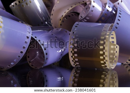 Close-up of a roll 35 mm photographic films on a glass desk - stock photo