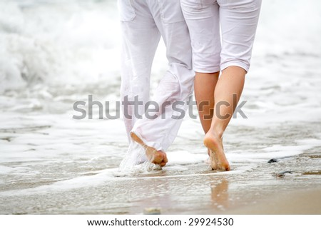 close-up of a romantic couple walking together along the beach