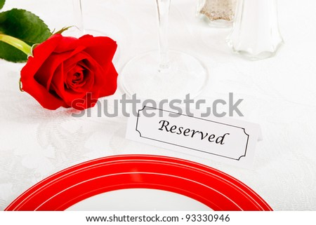 Close up of a romantic red and white place setting shows a reserved table at an elegant restaurant ready to celebrate an anniversary or Valentine's Day. - stock photo
