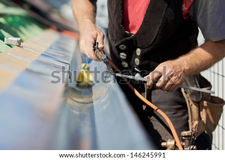 Close-up of a roofer applying weld into the gutter parts to assemble it - stock photo