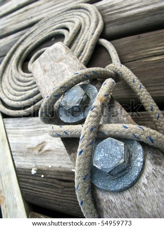 Close up of a rope tied onto cleat dockside - stock photo