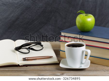 Close up of a rustic desktop of teacher with books, paper, pen, coffee, reading glasses a long with a green apple in front of chalkboard. Layout in horizontal format with copy space.  - stock photo