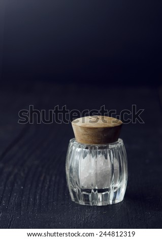 Close up of a rustic salt shaker over black wooden table - stock photo