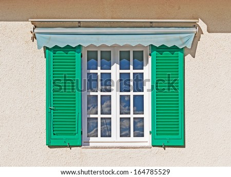 close up of a rustic window with the sky reflected in the glass - stock photo
