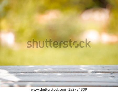 Close-up of a rustic wooden table on a green blurred background - stock photo