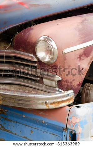 Close up of a rusty and broken front corner of an old vintage vehicle on rear of another - stock photo