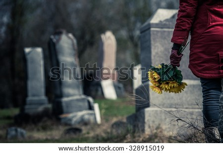Close-up of a Sad Woman Holding Sunflowers in front of a Loved one's Gravestone. Focus on the Bouquet. - stock photo