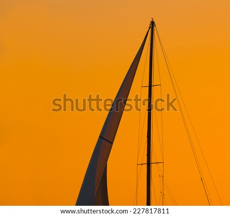 close up of a sail silhouette under an orange sky at sunset. Shot in Alghero, Sardinia. - stock photo
