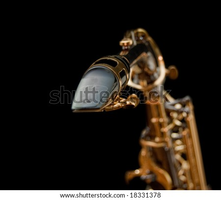 Close-up of a saxophone mouthpiece isolated in black background - stock photo