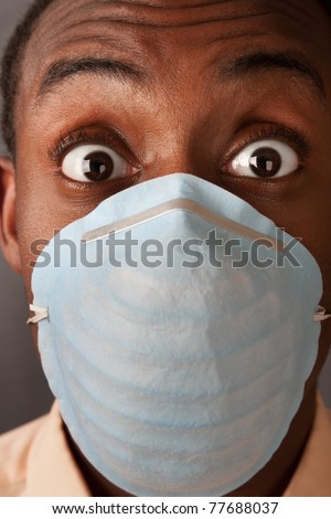 Close-up of a scared man in a surgical mask - stock photo