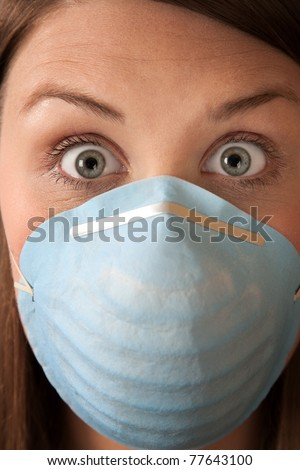 Close-up of a scared woman in a surgical mask - stock photo