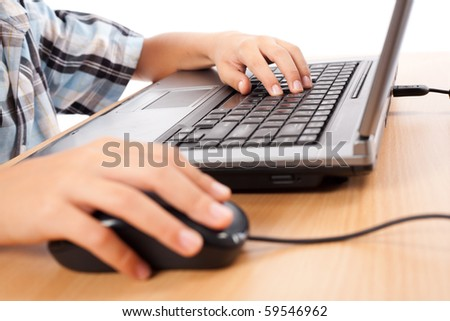 Close up of a schoolboy's hands using mouse and keyboard - stock photo