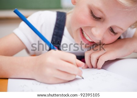 Close up of a schoolgirl writing something in a classroom