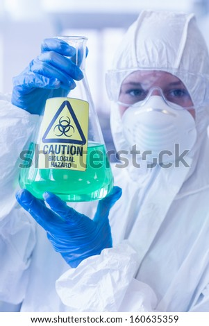 Close-up of a scientist in protective suit with hazardous blue chemical in flask at the laboratory - stock photo