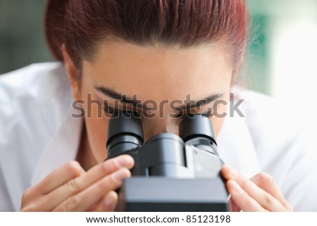 Close up of a scientist looking into a microscope in a laboratory - stock photo