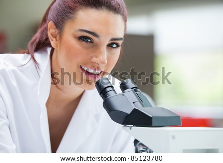Close up of a scientist posing with a microscope in a laboratory - stock photo