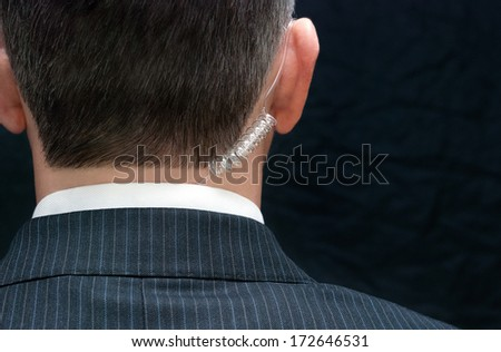 Close-up of a secret service agent, behind. - stock photo