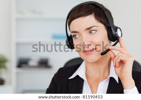 Close up of a secretary calling with a headset in her office - stock photo