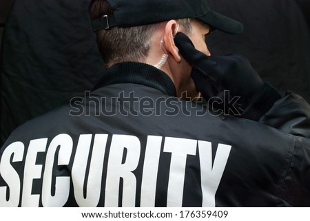 Close-up of a security guard listening to his earpiece. Back of jacket showing. - stock photo