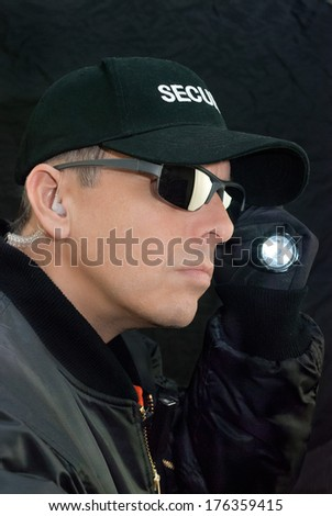 Close-up of a security guard searching with his flashlight. - stock photo