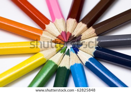 Close-up of a selection of colored pencil crayons, arranged like a color wheel.
