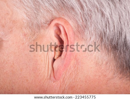 Close-up of a senior man's ear wearing a small hearing aid