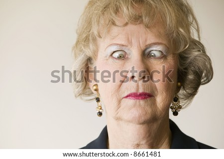 Close-up of a senior woman crossing her eyes. - stock photo