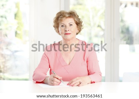 Close-up of a senior woman sitting at desk and making list.  - stock photo