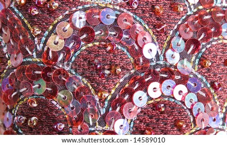 Close up of a sequin embroidery in red. - stock photo