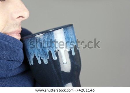 Close-up of a serene man holding his mug bundled in his robe. - stock photo