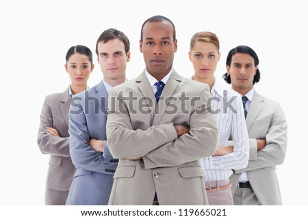 Close-up of a serious business team crossing their arms against white background - stock photo