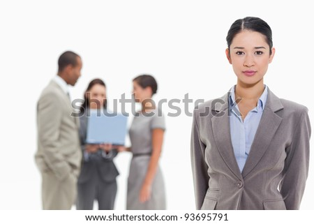 Close-up of a serious businesswoman smiling with co-workers watching a laptop in the background - stock photo