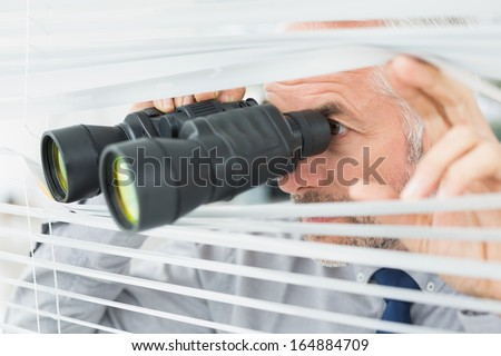 Close-up of a serious mature businessman peeking with binoculars through blinds in the office
