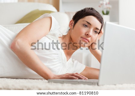 Close up of a serious woman relaxing with a laptop while lying on her carpet