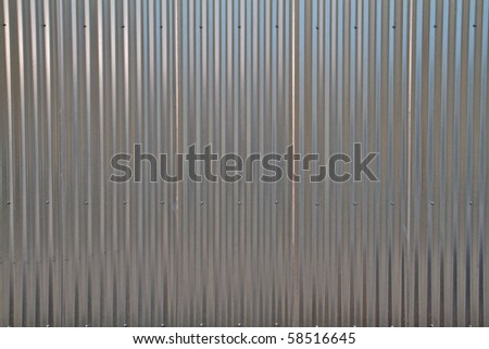 Close up of a shiny corregated steel wall - stock photo