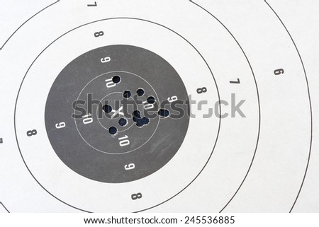 Close up of a shooting target and bullseye with bullet holes - stock photo