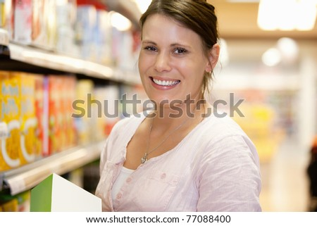 Close-up of a shopper in shopping centre smiling and looking at camera - stock photo