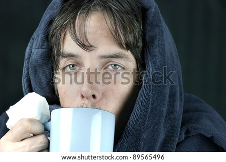 Close-up of a sick man holding a tissue drinking from a hot mug. - stock photo