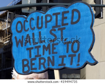"Close up of a sign at a Bernie Sanders rally saying ""Occupied Wall Street, Time to Bern It"" in downtown Asheville, NC"