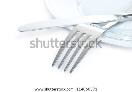 Close up of a silver knife and fork on plate isolated on white background - stock photo