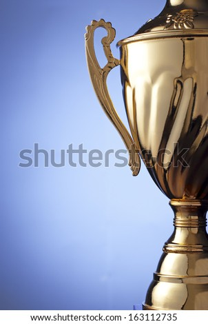 Close up of a silver metal trophy with a lid and handle to be presented to the winner of a competition, contest or championship on a blue background with copyspace - stock photo