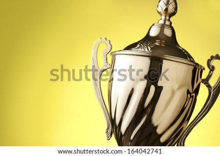 Close up of a silver metal trophy with a lid and handle to be presented to the winner of a competition, contest or championship on a yellow background with copyspace - stock photo