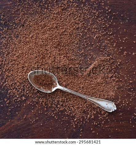 close up of  a silver spoon and chocolate powder on wooden table - studio shot  from above - stock photo