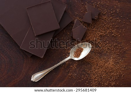 close up of  a silver spoon, cocoa powder and chocolate from above - studio shot - stock photo