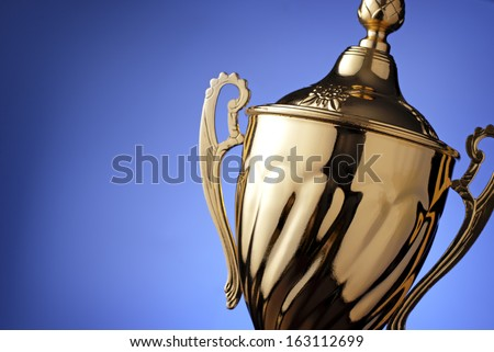 Close up of a silver trophy prize with an ornate lid and handles for the winner of a championship event or competition on blue with copyspace - stock photo