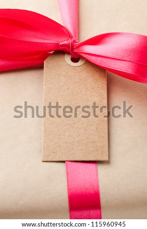 Close-up of a simple gift package with a red ribbon and small card. - stock photo