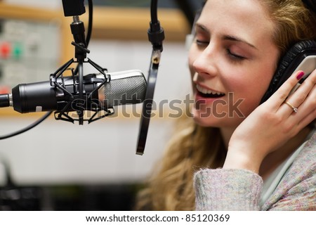 Close up of a singer recording a track in a studio - stock photo