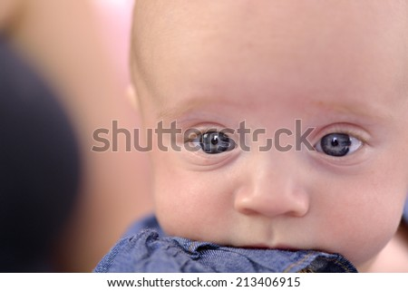 Close-up of a six month baby girl with rosy cheeks nibbling her dres - stock photo