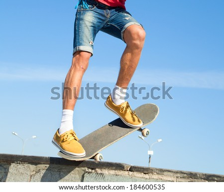 Close up of a skateboarders feet while skating on concrete at the skate park