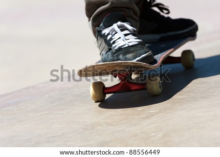 Close up of a skateboarders feet while skating on concrete.  Shallow depth of field. - stock photo